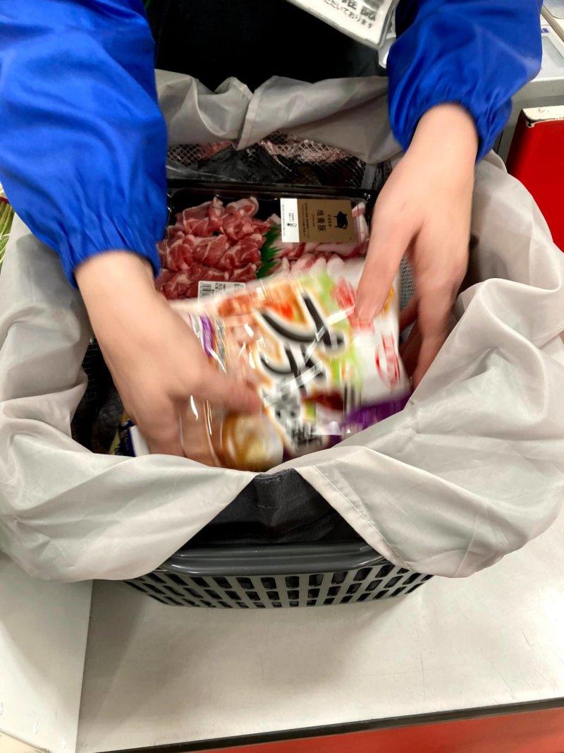 スーパーの店員さんが買い物かごバッグbon momentに商品を詰めてくれているところ