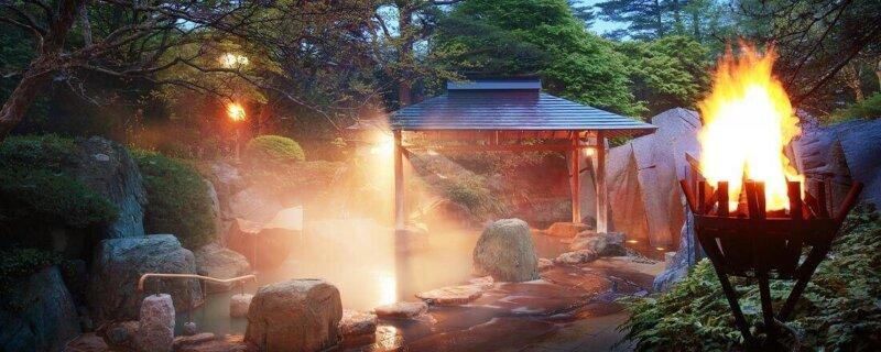 秋保温泉篝火の湯緑水亭の露天風呂に篝火が灯された様子