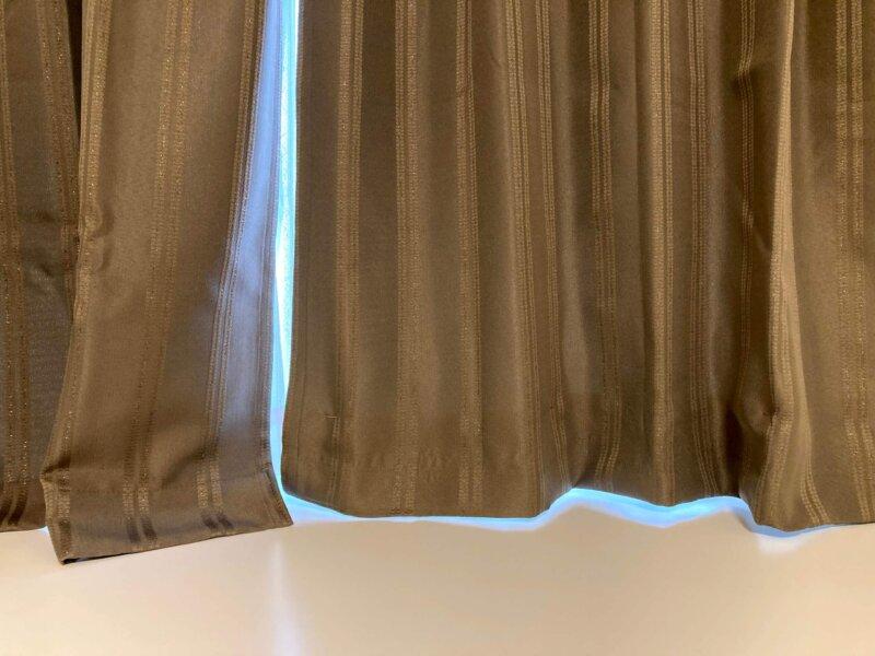 まち針で仮留めした状態でカーテンをかけて長さを確認しているところ
