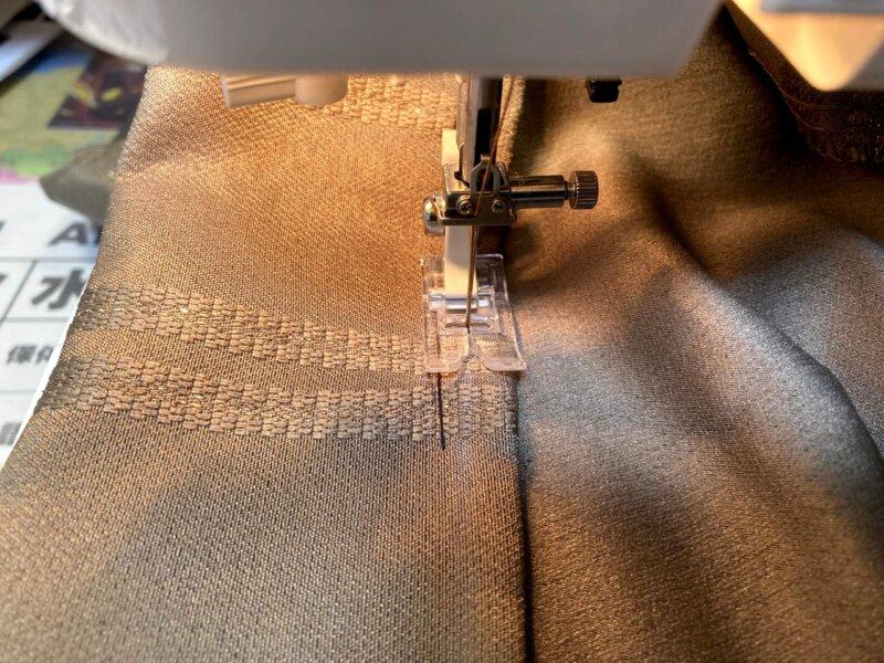 ミシンでカーテンの裾を縫っているところ