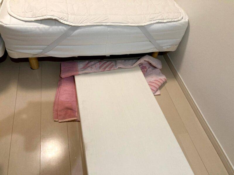 寝室クローゼットの折れ戸をタオルケットで滑らせながらベッドの下に収納するところ